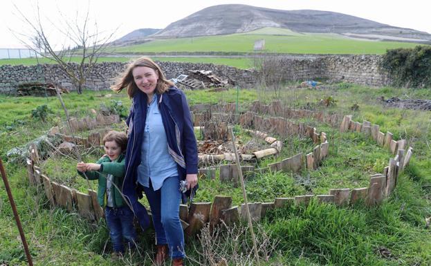 La irlandesa Emma y su hijo, el único niño que reside en Hornillos del Camino, en su huerta. /APM
